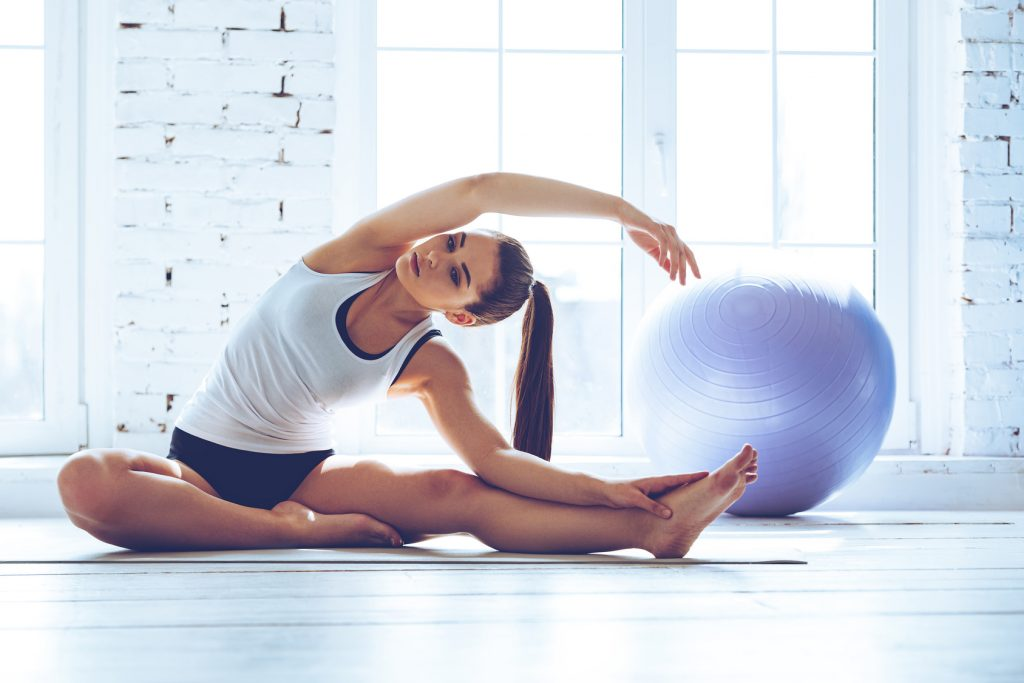Beautiful and flexible. Young beautiful young woman in sportswear doing stretching while sitting in front of window at gym